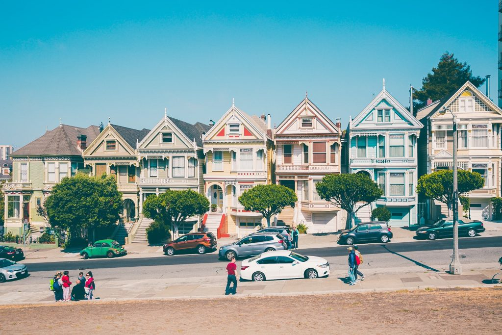 pastel colored houses on a hill call the painted ladies in san francisco